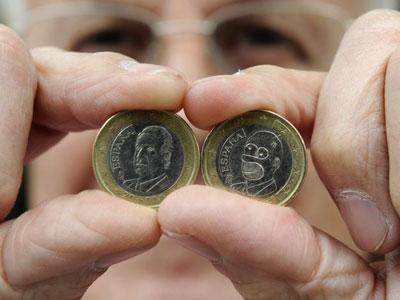Jose Martinez shows Spain's official one euro coin beside the one he found in his cash register
