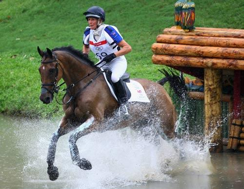 Mary King and Call Again Cavalier go through the water jump during the cross country section of the equestrian event at the Beas River Equestrian Venue