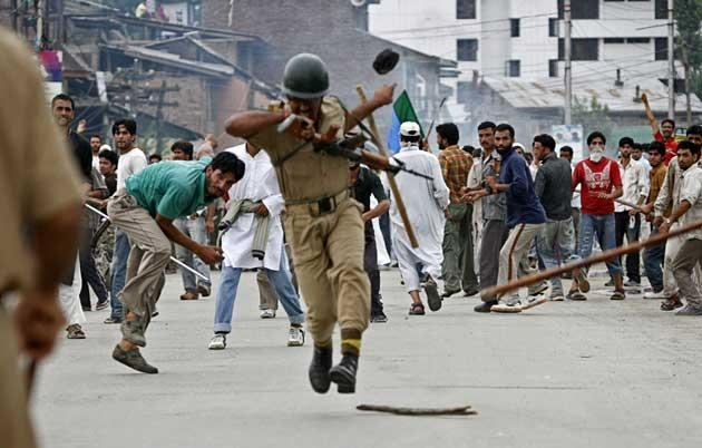 An Indian policeman is hit by an object thrown by a protester in Srinagar yesterday