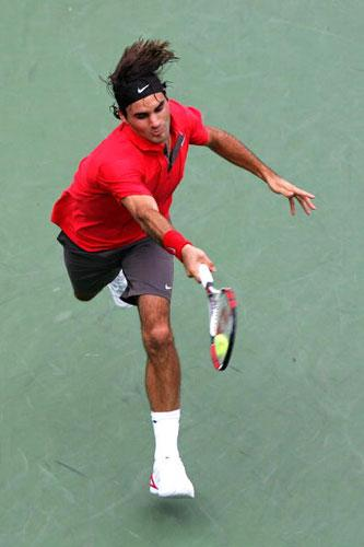 Roger Federer, the defending US Open champion, races to hit a return to Novak Djokovic in their semi-final on Saturday