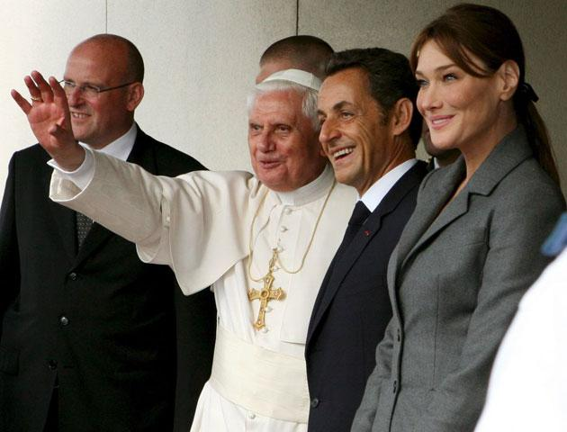 Pope Benedict XVI waves to crowds of onlookers as he is welcomed by the French President Nicolas Sarkozy and his wife