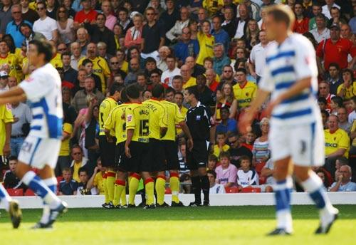 Referee Stuart Attwell is surrounded by Watford players after he awarded a goal to Reading that should never have been given
