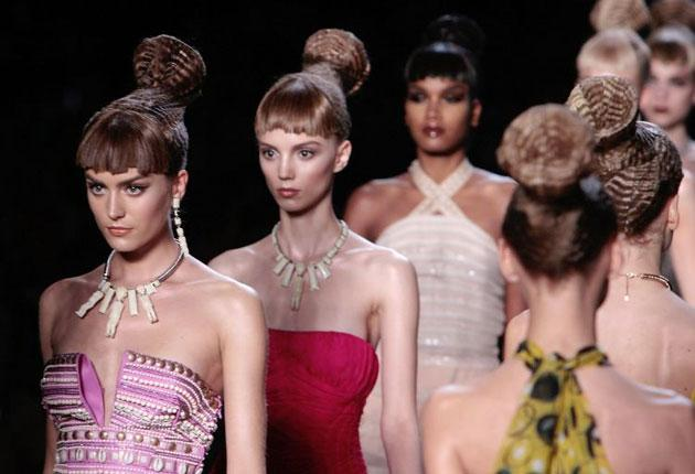 Models present creations by British designer John Galliano for Christian Dior