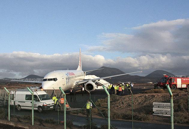 Airport emergency personnel stand next to an Air Europa plane that went off the runway as it was landing in Lanzarote today