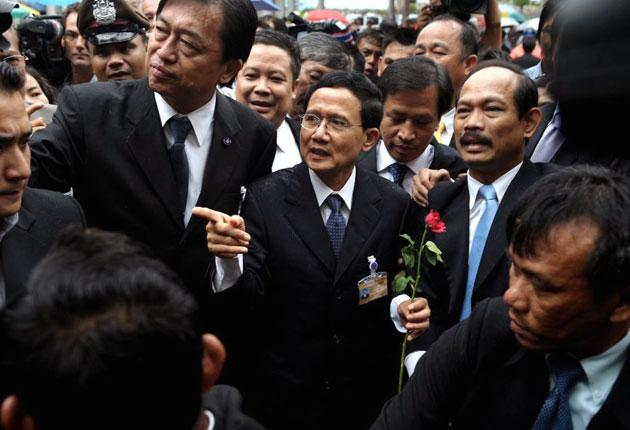 The Thai Prime Minister, Somchai Wongsawat, (centre), has been banned from politics for five years and the ruling party dissolved over voting fraud