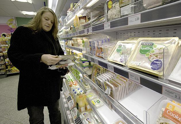 A shopper inspects products at a local shop in Belfast, Northern Ireland. Many pork products have already been withdrawn. Now there is concern about beef herds