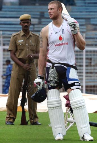 An Indian policeman stands guard as Andrew Flintoff waits to practise in the nets at the MA Chidambaram Stadium in Chennai yesterday ahead of the first Test between India and England, which starts tomorrow
