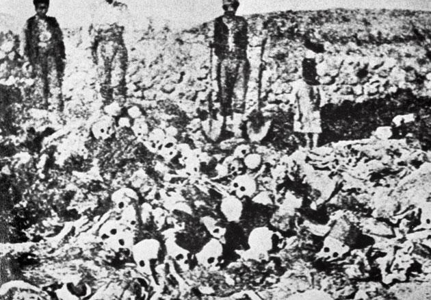 Men standing besides the skulls and corpses of Armenian victims of turkish deportation in the second part of the 1910's