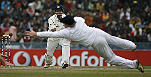 England's Ian Bell dives to stop the ball as India's Rahul Dravid watches on the first day of their second cricket test match in Mohali