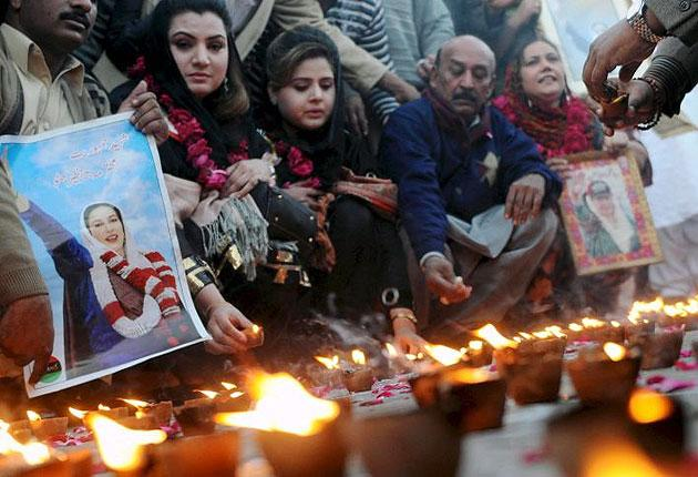 Supporters of the late Benazir Bhutto burn candles in Lahore just last week. The Pakistani government has decided to officially observe the first anniversary of her death on 27 December