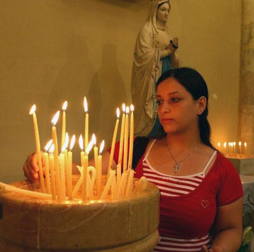 "A Palestinian Christian woman lights candles in the Latin Patriarchal Seminar ""Bishara"" church in the West Bank town of Bethlehem"