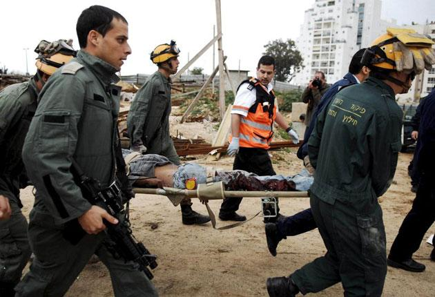 Israeli rescue personnel carry a wounded Bedouin Arab construction worker to an ambulance after the site was hit by a Grad missile fired by Palestinian militants