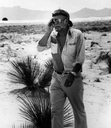 Sam Peckinpah walking across a saltmarsh in sweltering heat in the late Seventies
