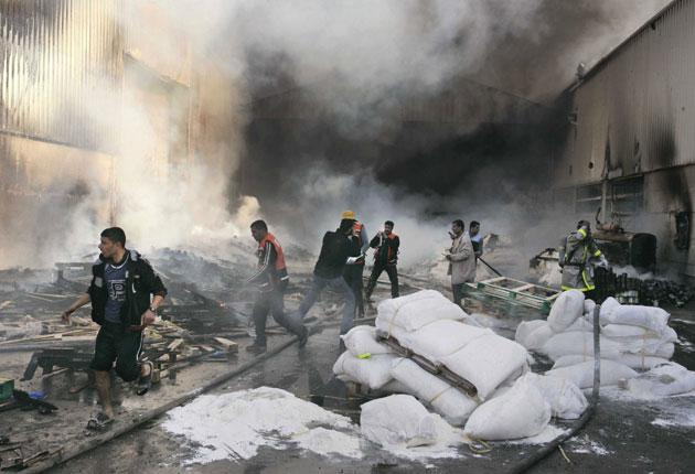United Nations workers and Palestinian firefighters try to put out fires and save bags of food aid at the UN headquarters after it was hit by Israeli bombardment in Gaza yesterday