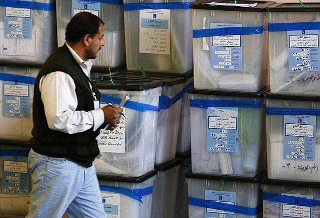 An electoral worker checks ballot boxes at a counting centre in Basra