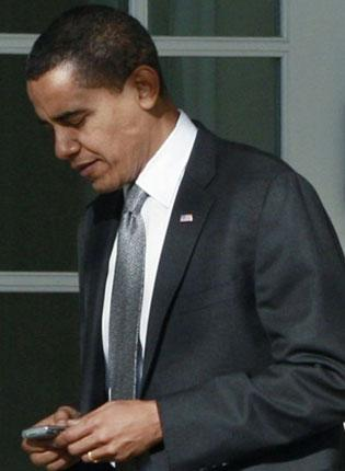 Barack Obama using his Blackberry on his way to the Oval Office