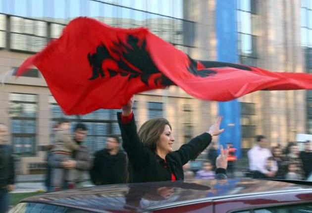 A Kosovan celebrates the country's declaration of independence a year ago by flying the Albanian flag outside the EU headquarters in Brussels