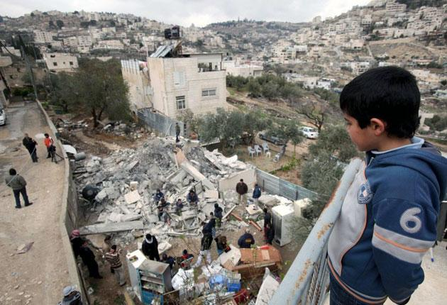 Palestinians scour the rubble of a home demolished in East Jerusalem this week. Officials want to pull down 88 more homes