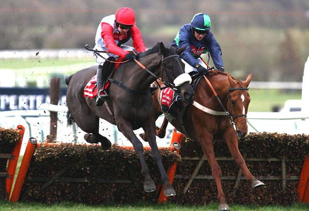 Big Buck's and Ruby Walsh (left) tussle with Punchestowns and Barry Geraghty at the final flight before going on to claim yesterday's World Hurdle