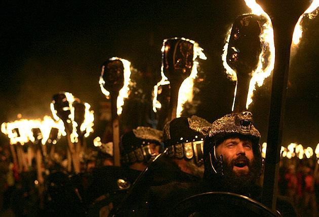 Jarl Squad Vikings march while carrying lit torches to set fire to a Viking longboat during the Up Helly Aa festival in Lerwick, the Shetland Islands in northern Scotland