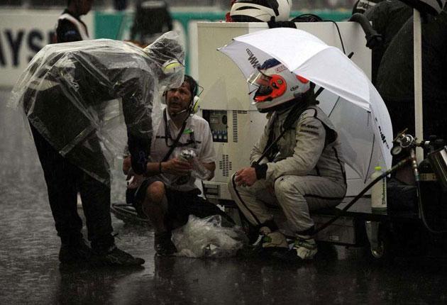 Brawn's Rubens Barrichello talks to his drenched mechanics