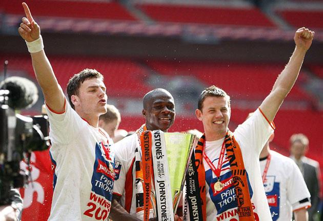 Luton Town's Chris Martin (left) and Tom Craddock (right) celebrate their side's victory yesterday in the Johnstone's Paint Trophy, secured by a fine goal in extra time from Claude Gnakpa (centre)