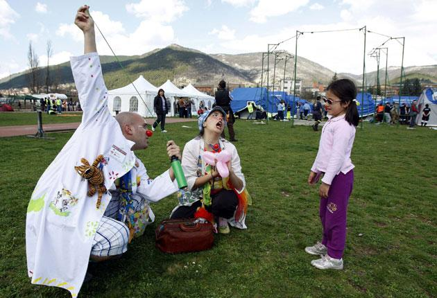 Clowns perform tricks for a child at a tent camp for earthquake victims in L'Aquila