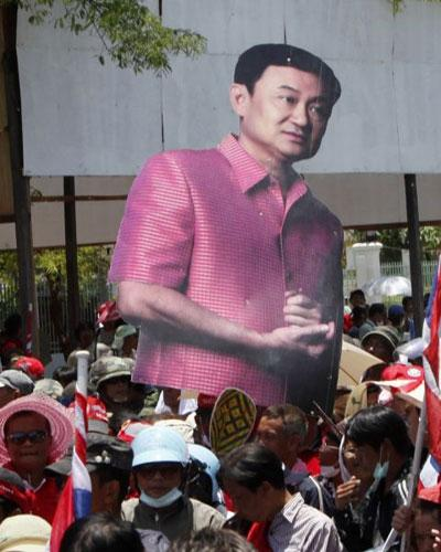 Supporters of Thaksin Shinawatra carry an image of the ousted leader in Bangkok