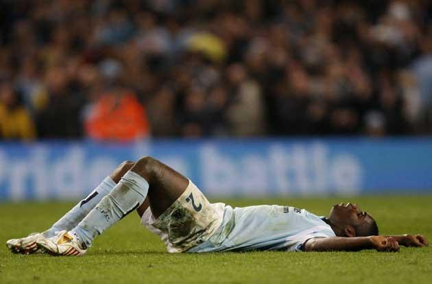 Micah Richards, who finished the match almost a passenger, lies exhausted on the pitch after Manchester City's exit from the Uefa Cup at Eastlands last night