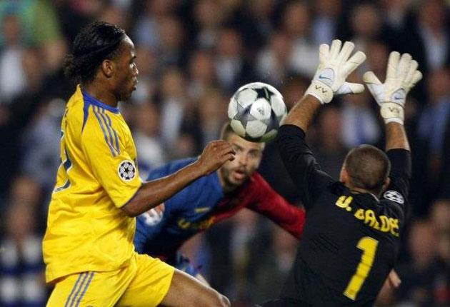 Barcelona's goalkeeper Victor Valdes saves a shot from Chelsea's Didier Drogba as Barcelona's Gerard Pique looks on during their Champions League semi-final, first leg match at the Nou Camp