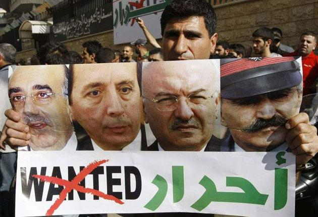 A man carries a poster showing the released Lebanese generals, with the word 'Wanted' replaced by 'Free'
