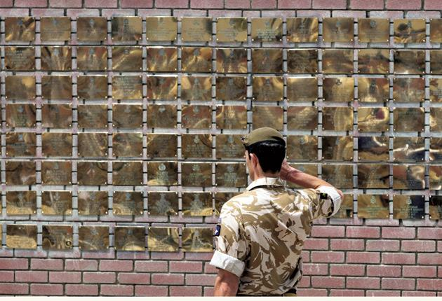 A soldier salutes the Basra memorial wall at Contingency Operating Base yesterday