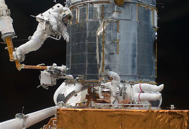 In this photo provided by Nasa, astronaut Andrew Feustel, left, STS-125 mission specialist, navigates near the Hubble Space Telescope on the end of the remote manipulator system arm, controlled from inside Atlantis' crew cabin as astronaut John Grunsfeld,