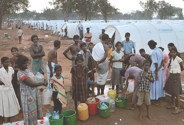 Tamil refugees queue for water. Most are not allowed to leave the camps and say there is not enough to drink