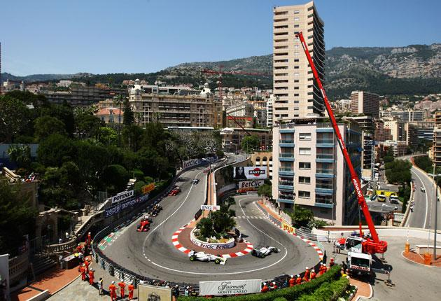 Jenson Button leads his Brawn team-mate Rubens Barrichello and the rest of the field around the Fairmont Hotel corner in Monaco yesterday