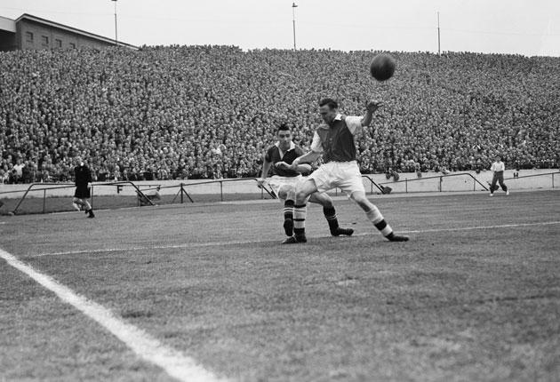 Campbell (left) crosses the ball under pressure from Arsenal's Lionel Smith at Stamford Bridge in 1949