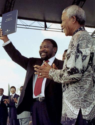 Cyril Ramaphosa holds the newly signed South African constitution in 1996 as the President Nelson Mandela looks on