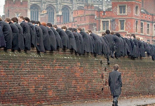 Eton College boys in their traditional uniform watch the school's 'wall game'