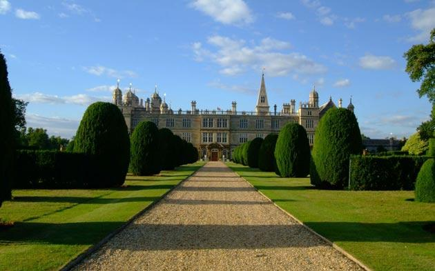 A gravel driveway leads the eye past lawns and topiary towards the south entrance of Burghley House