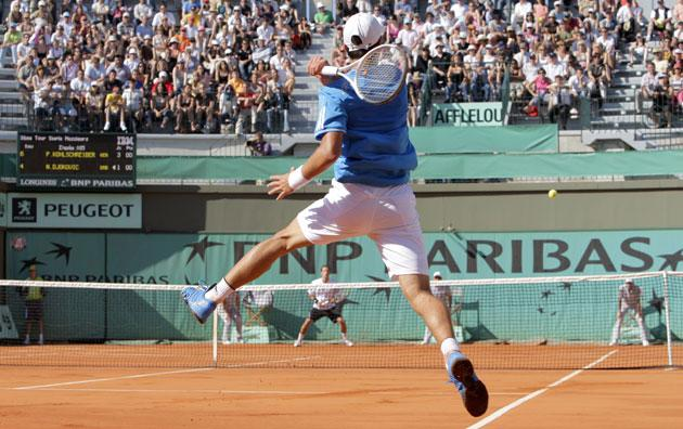 Novak Djokovic returns the ball to Germany's Philipp Kohlschreiber during the world No 4's unexpected defeat at Roland Garros yesterday