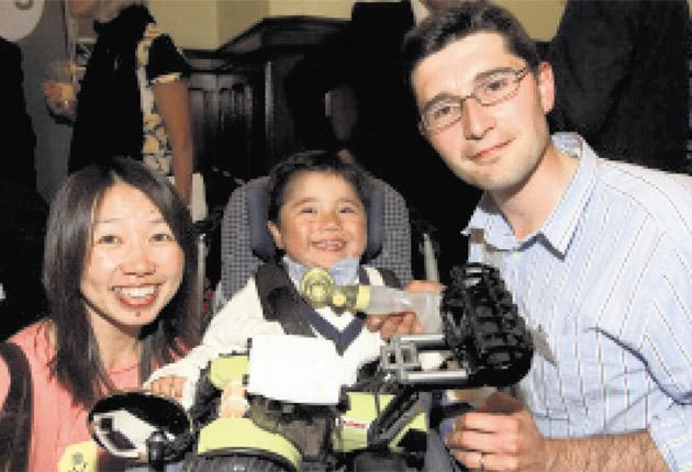 Kazumi and Neil Puttick with their five-year-old son Sam, who was paralysed from the neck down after a car accident when he was just 16 months old