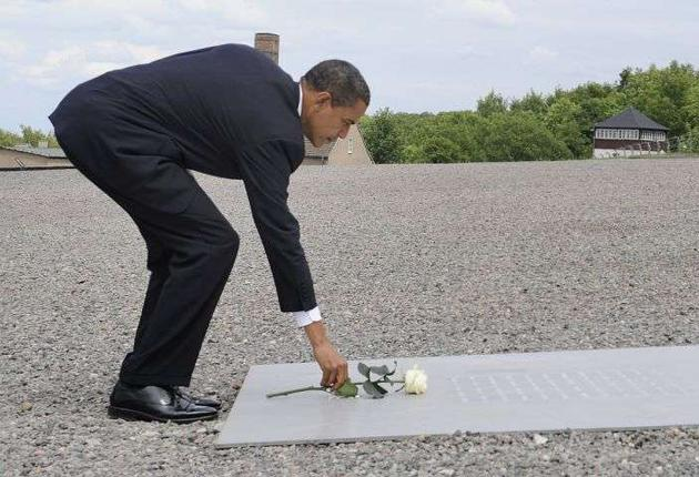 Barack Obama puts down a rose at the former Buchenwald concentration camp yesterday. He said the memorial was the 'ultimate rebuke' to Holocaust deniers - remarks aimed at Iran