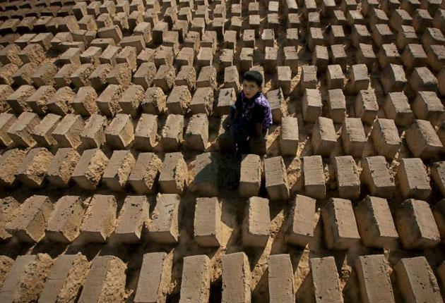 A Palestinian boy sits on a row of adobe bricks in the town of Rafah, the centre of Gaza's mud industry