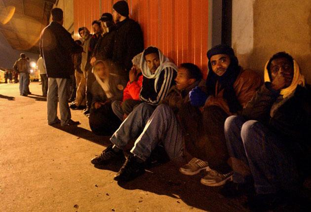 Would-be immigrants and applicants for asylum in the UK wait outside a food delivery service in Calais, France