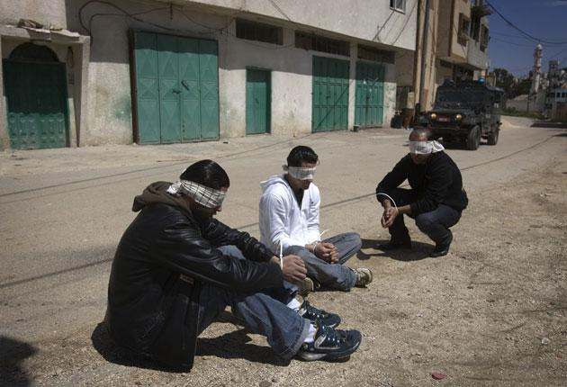 Blindfolded Palestinian men sit with hands tied after being detained during the Israeli operation in Hares on 26 March