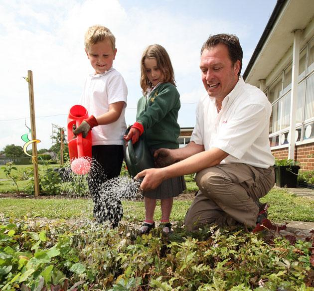 Hayden Smith, seven, and Yasmin Haigh, six, help Jeremy Swallow from Marshalls water in their new plants