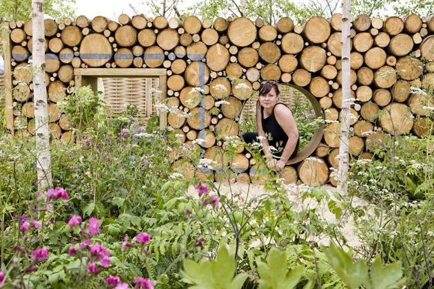 The circle of life: Emma peers through a steel porthole in Hallenga and Bugg's insect-friendly log wall