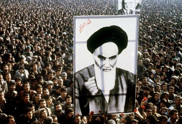 Protesters hold up a poster of Ayatollah Khomeini during a demonstration against the Shah on 1 January 1979
