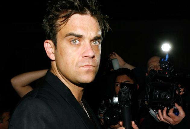 A Bahamian police commander says detectives are investigating a weekend robbery of two paparazzi shortly after they snapped pop idol Robbie Williams on a beach.