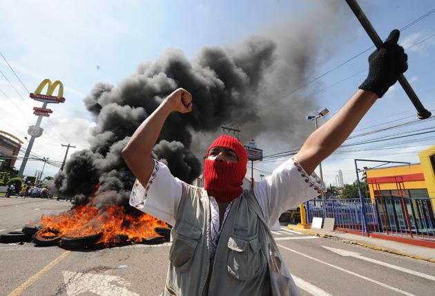 Aprotester demonstrates outside the presidential palace in Tegucigalpa after soldiers stormed the building and took President Manuel Zelaya into custody